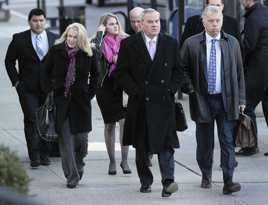 Former Connecticut Gov. John Rowland, center, arrives with wife Patty, left, and attorney Reid Weingarten, right, at federal court in New Haven, Wednesday, March 18, 2015, in New Haven, Conn. A federal court jury in New Haven convicted Rowland in September of federal charges that he conspired to hide payment for work on two congressional campaigns. His sentencing on Wednesday will come 10 years to the day that he was sentenced to a year and a day in prison for accepting illegal gifts while in office, including trips and improvements to his lakeside cottage. (AP Photo/Jessica Hill)