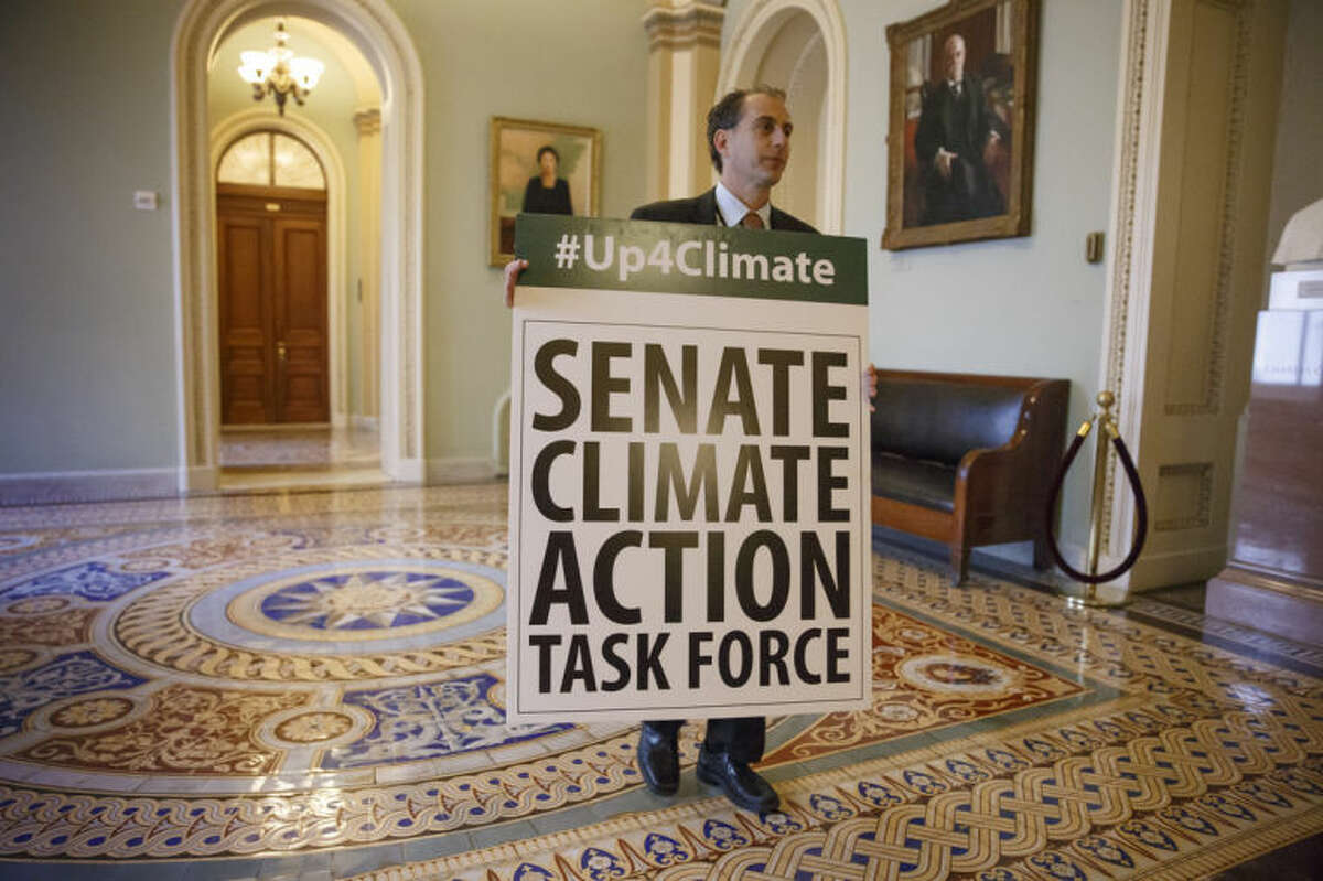 Joe Mendelson, the majority chief climate counsel with the Senate Committee on Environment, waits outside the Senate chamber on Capitol Hill in Washington, Tuesday, March 11, 2014, as Democratic senators finish an all-night session warning of the devastation from climate change and the danger of inaction. (AP Photo/J. Scott Applewhite)