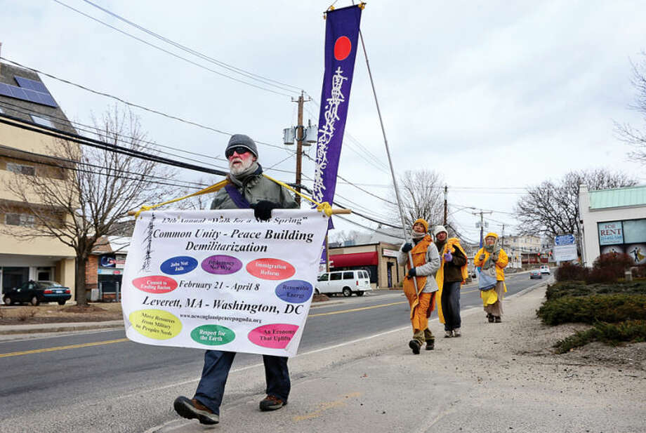 "Hour photo / Erik Trautmann George Esworthy and members of the New England Peace Pagoda continue on their 13th annual ""Walk for a New Spring"" along Route 1 in Norwalk Thursday morning as their journey takes them from Leverett, Massachusetts to Washington DC promoting a message of peace and environmental protection."