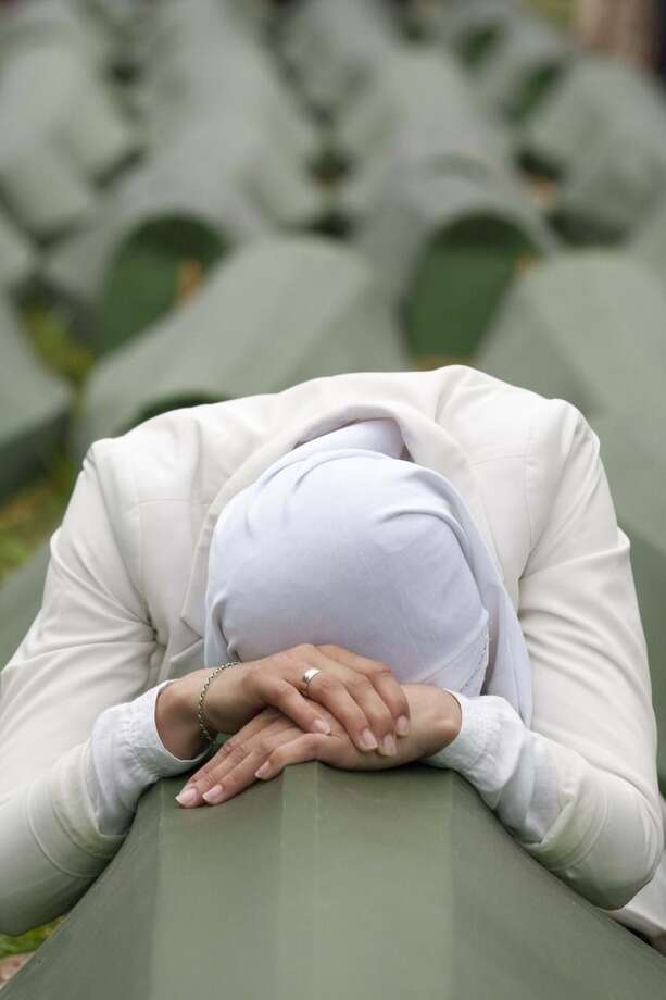 FILE - In this Friday July 11, 2014 file photo, a Bosnian Muslim woman cries in front of the coffin of her relative during a mass funeral at the memorial center Potocari, near Srebrenica. Serbian police arrested eight men Wednesday March 18, 2015, who are accused of taking part in the slaughter of more than 1,000 Muslims at a warehouse on the outskirts of Srebrenica. Altogether, more than 8,000 Bosnian Muslim men and boys were killed in the eastern Bosnian enclave by the Serbs in 1995 — the only atrocity in Europe to be labeled genocide by the United Nations since World War II. (AP Photo/Amel Emric, File)