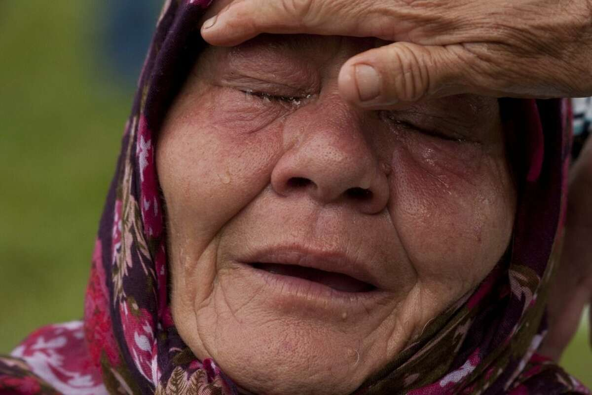 FILE - In this Friday July 11, 2014 file photo, a Bosnian Muslim woman Senija Rizvanovic cries near the graves of her two sons, in Srebrenica, Bosnia. Serbian police arrested eight men Wednesday March 18, 2015, who are accused of taking part in the slaughter of more than 1,000 Muslims at a warehouse on the outskirts of Srebrenica. Altogether, more than 8,000 Bosnian Muslim men and boys were killed in the eastern Bosnian enclave by the Serbs in 1995 - the only atrocity in Europe to be labeled genocide by the United Nations since World War II. (AP Photo/Amel Emric, File)