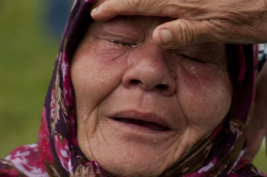 FILE - In this Friday July 11, 2014 file photo, a Bosnian Muslim woman Senija Rizvanovic cries near the graves of her two sons, in Srebrenica, Bosnia. Serbian police arrested eight men Wednesday March 18, 2015, who are accused of taking part in the slaughter of more than 1,000 Muslims at a warehouse on the outskirts of Srebrenica. Altogether, more than 8,000 Bosnian Muslim men and boys were killed in the eastern Bosnian enclave by the Serbs in 1995 — the only atrocity in Europe to be labeled genocide by the United Nations since World War II. (AP Photo/Amel Emric, File)