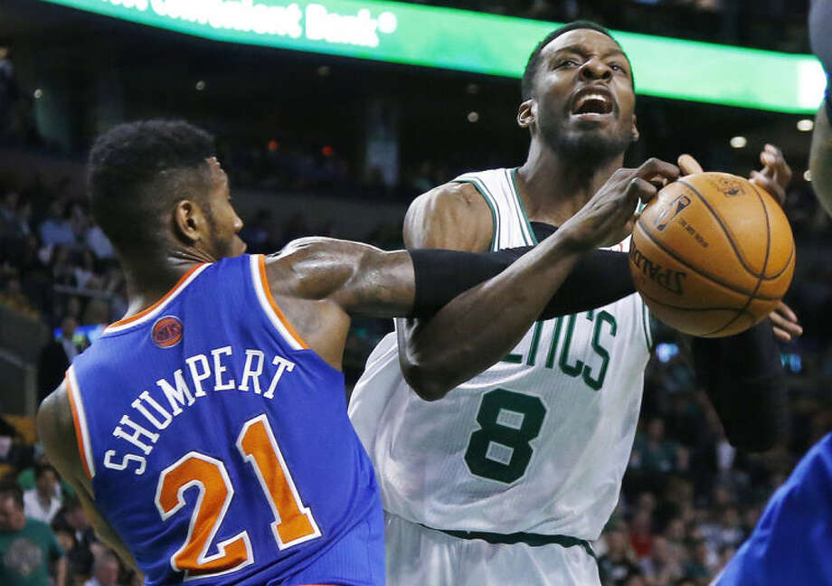 Boston Celtics forward Jeff Green (8) is fouled by New York Knicks guard Iman Shumpert (21) while driving to the hoop during the second quarter of an NBA basketball game in Boston, Wednesday, March 12, 2014. (AP Photo/Elise Amendola)