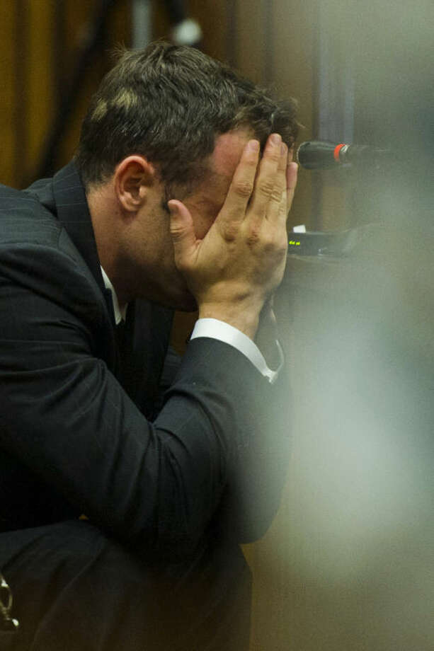 Oscar Pistorius covers his face with his hands as he listens to forensic evidence during his trial in court in Pretoria, South Africa, Thursday, March 13, 2014. Pistorius is charged with the shooting death of his girlfriend Reeva Steenkamp, on Valentines Day in 2013. (AP Photo/Alet Pretorius, Pool)