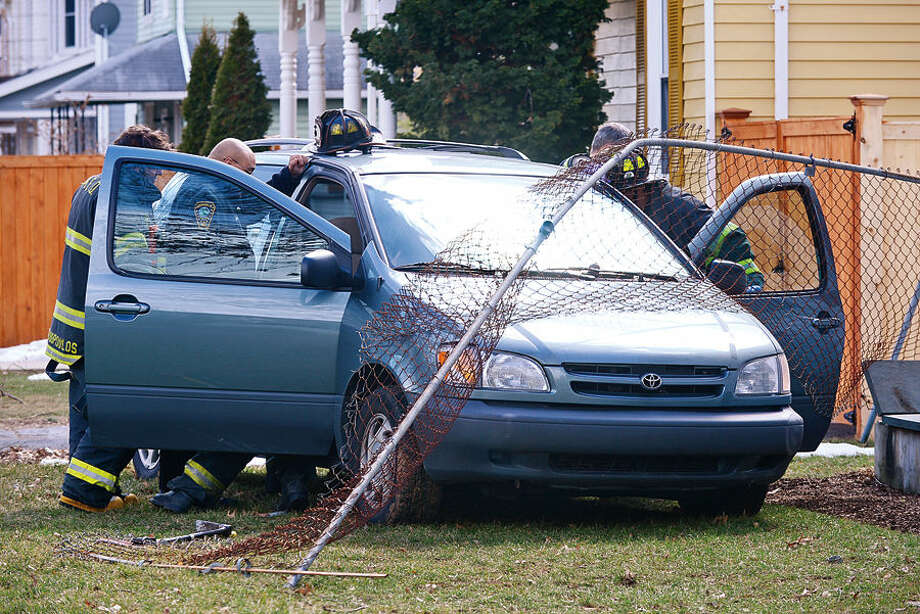 Hour photo / Erik Trautmann Emergency personnel respond to a motor vehicle accident on Gregory Boulevard where an elderly man drove his minivan across two lawns and through a chain link fence Wednesday afternoon.