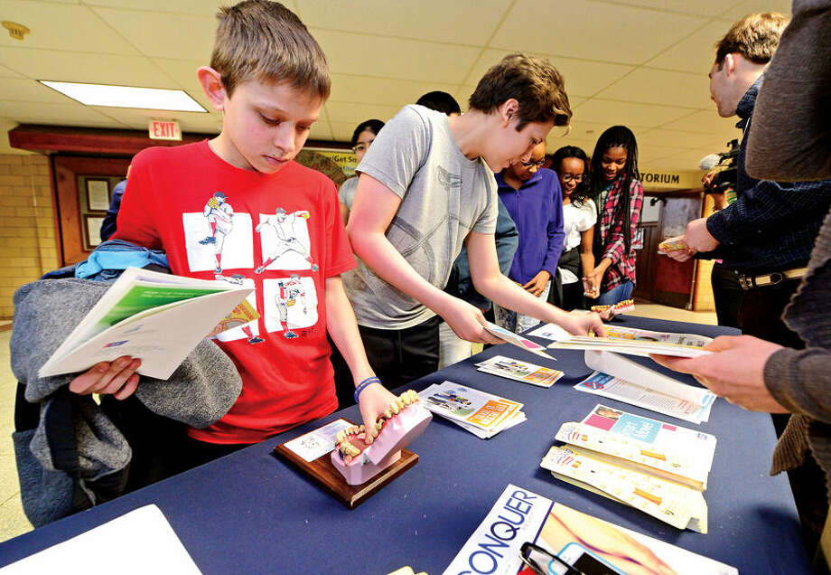 Hour photo / Erik Trautmann 8th grader Kristofer Dushi looks over a literature presented by the School Based Health Center (SBHC) at Dolan Middle School which teaches students about the dangers of tobacco following a special assembly to commemorate National Kick Butts Day featuring Stamford Hospital Pulmonologist Paul Sachs, M.D.