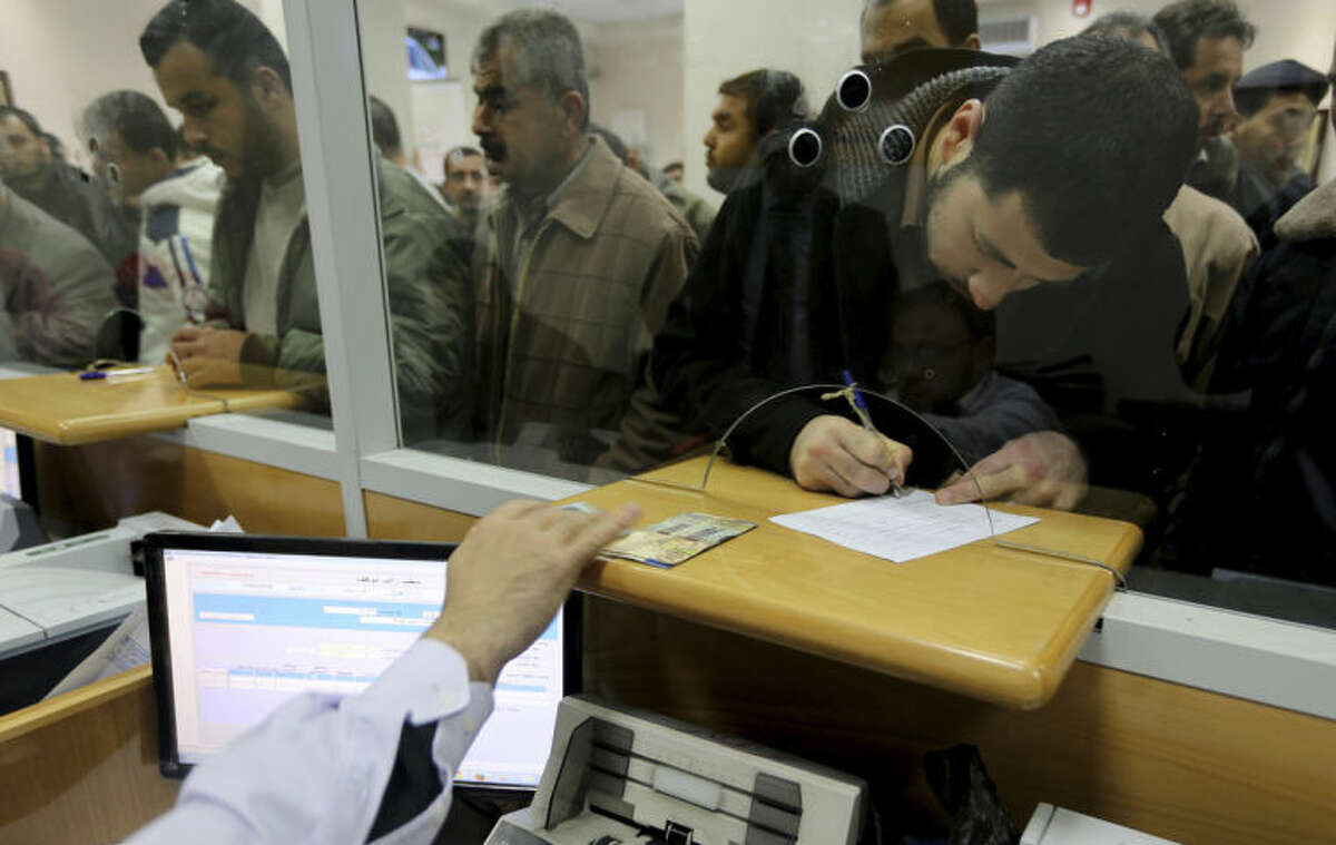 In this Wednesday, March 12, 2014 photo, a Palestinian Hamas employee picks up his salary as others wait in queue at the post office in Gaza City in the northern Gaza Strip. Gaza's Hamas rulers have been hit by the worst economic crisis since seizing the territory seven years ago and face growing discontent, even among core supporters, because there's no sign of relief from a blockade enforced not only by Israel but also by a suddenly hostile Egypt. (AP Photo/Hatem Moussa)