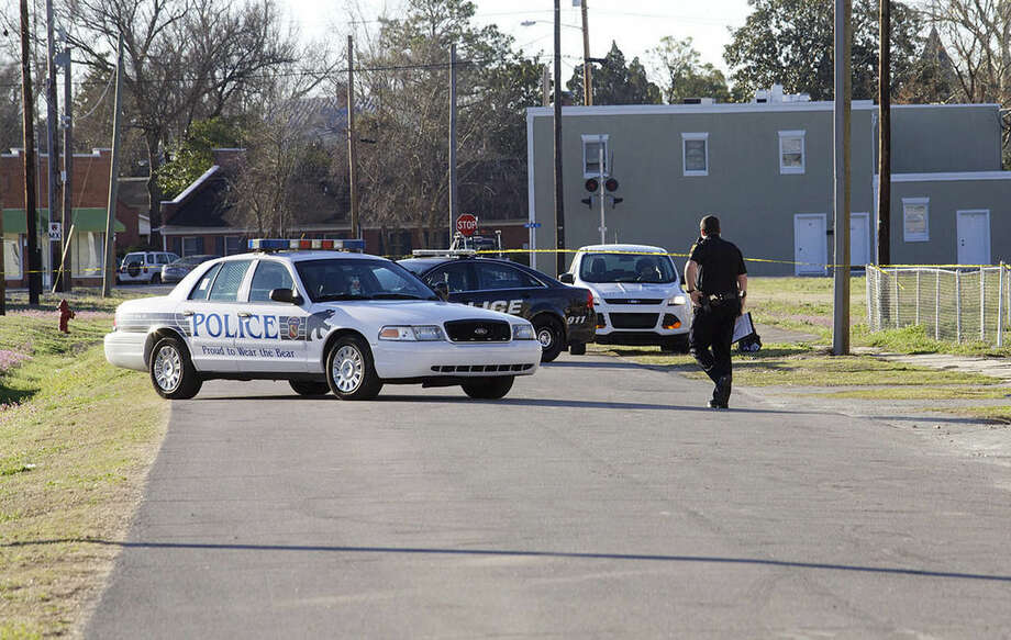 A police officer walks to his car during an investigation, Wednesday, March 18, 2015, of a triple homicide that took place late Tuesday, at a residence, in New Bern, N.C. Three children were stabbed to death and two other people were wounded in the attack. (AP Photo, Sun Journal, Bill Hand)