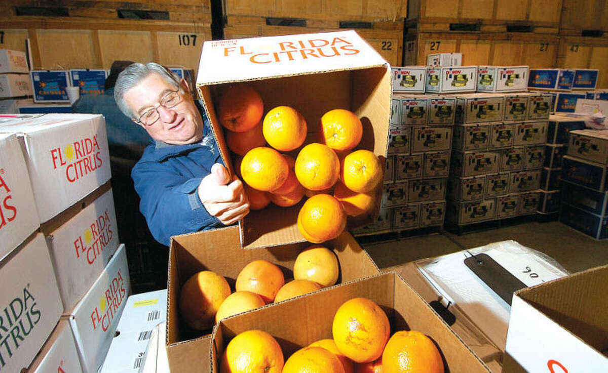 Wilton Kiwanis Club President-Elect Paul Hannah unloads a box of grapefruits and oranges for the group's annual citrus drive fundraiser.