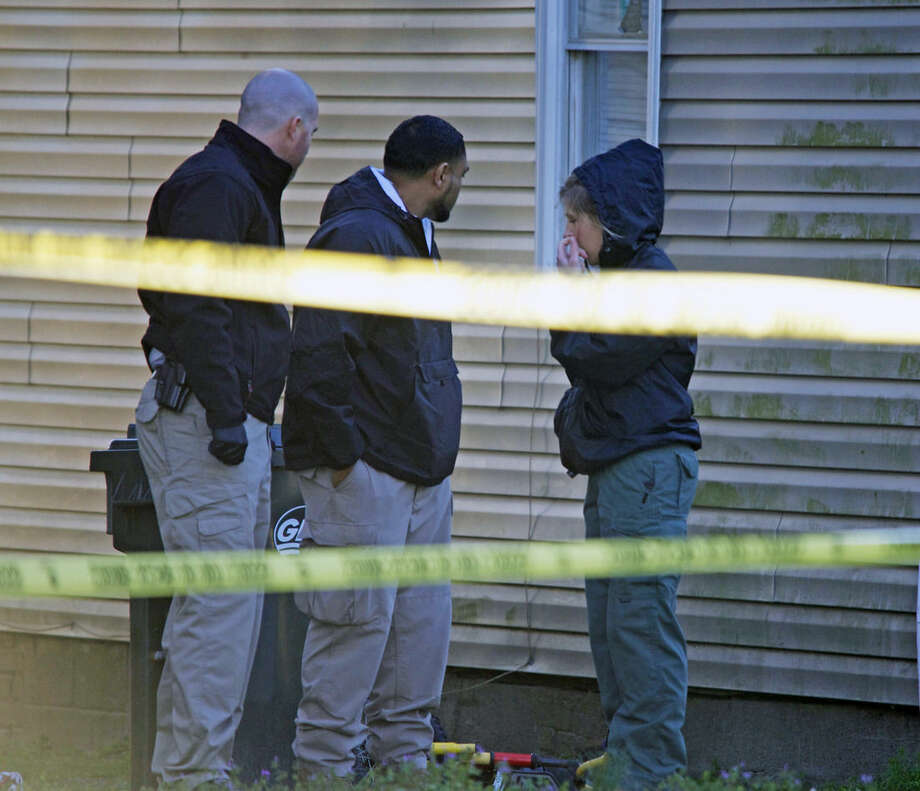Investigators work, Wednesday, March 18, 2015, in the backyard of a home where a triple homicide took place late Tuesday, in New Bern, N.C. Three children were stabbed to death and two other people were wounded in the attack. (AP Photo, Sun Journal, Bill Hand)