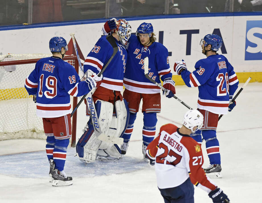 New York Rangers goaltender Cam Talbot (33) celebrates with Carl Hagelin, center, Dominic Moore (28) and Jesper Fast (19) after the Rangers defeated the Florida Panthers 2-1 during the third period of an NHL hockey game Sunday, March 15, 2015, at Madison Square Garden in New York. (AP Photo/Bill Kostroun)