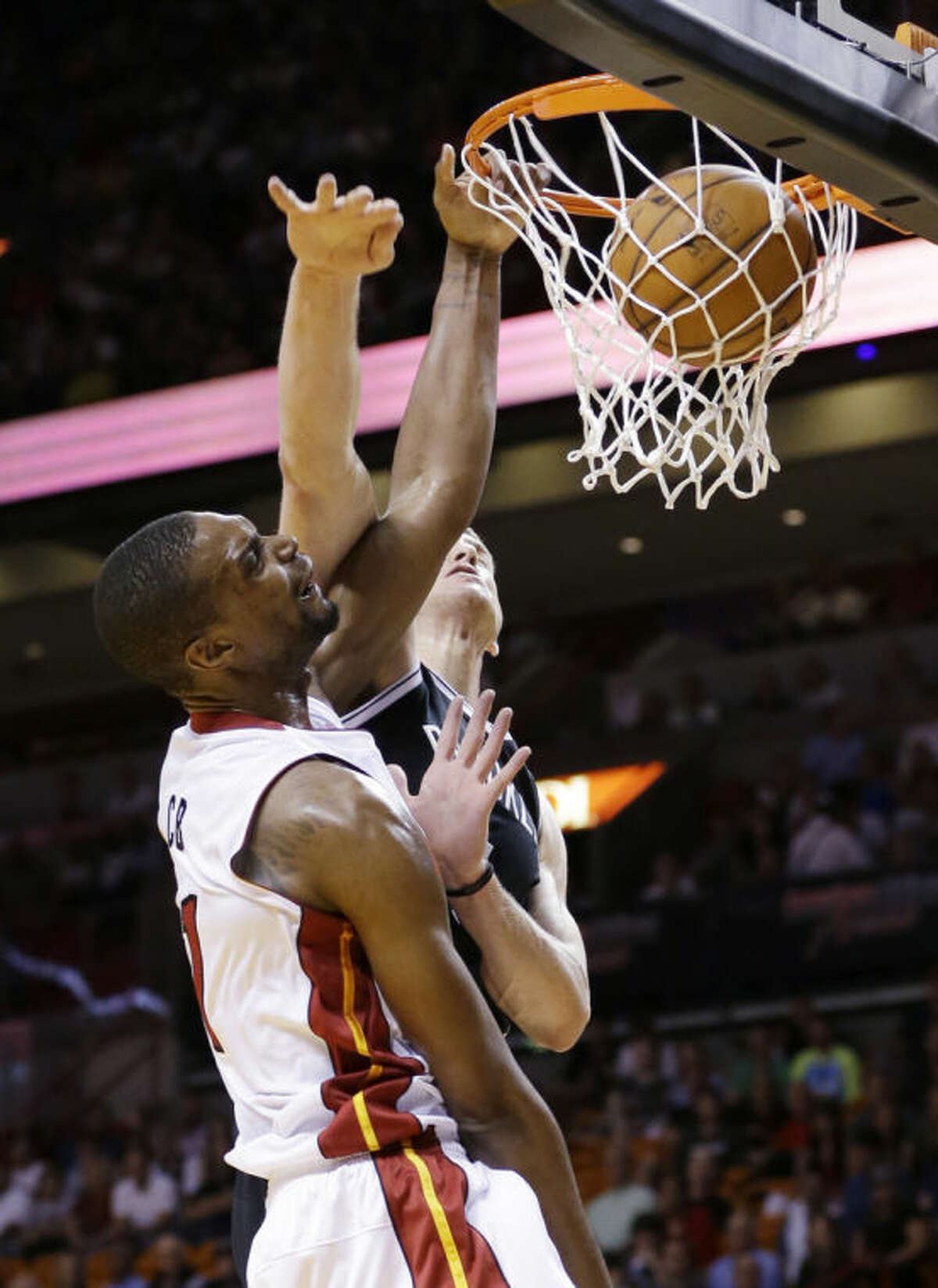 Miami Heat center Chris Bosh, foreground dunks the ball against Brooklyn Nets forward Mason Plumlee during the first half of an NBA basketball game, Wednesday, March 12, 2014, in Miami. (AP Photo/Wilfredo Lee)