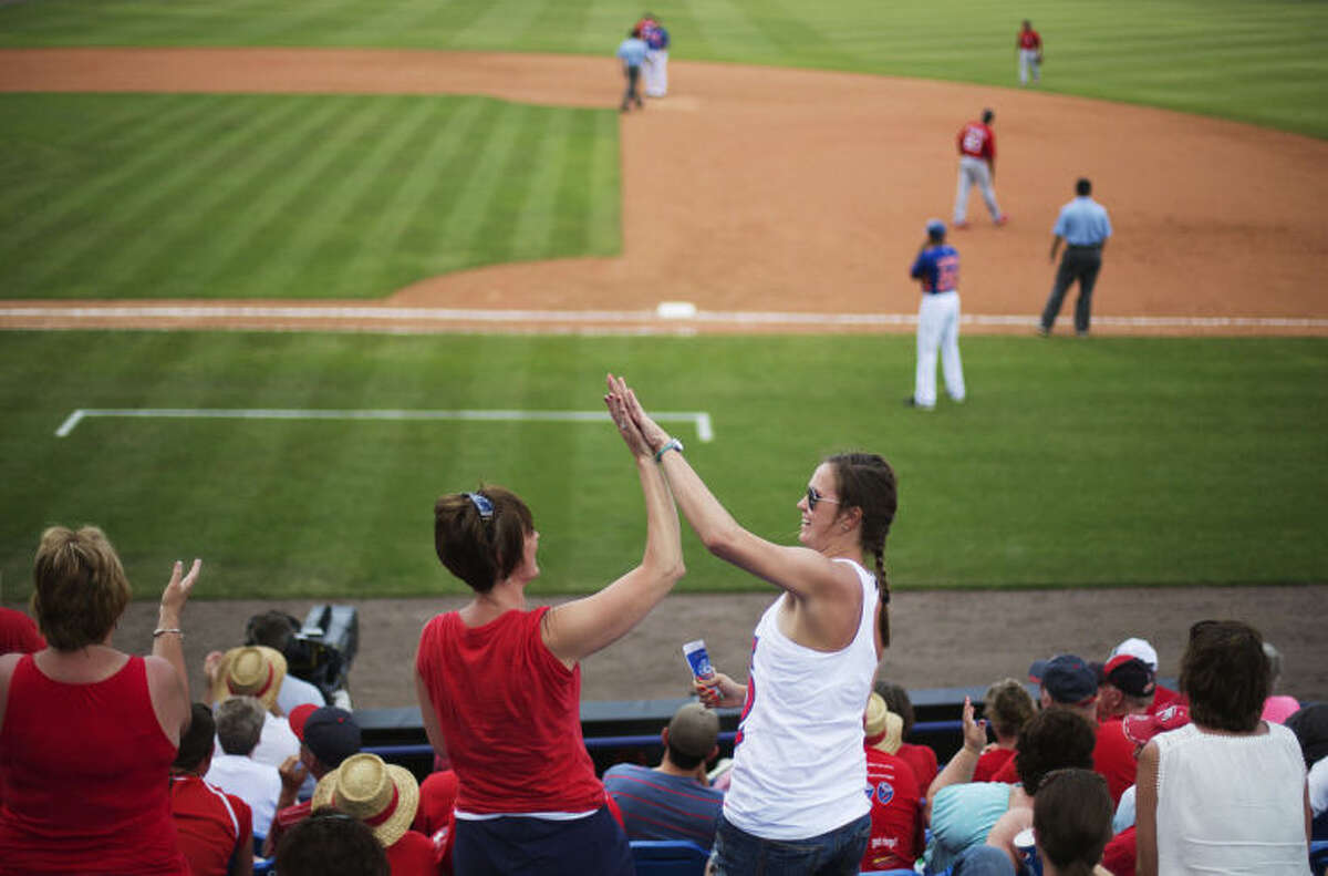 St. Louis Cardinals fans high-five one another after New York Mets' Brandon Allen grounded out putting the Cardinals one out away from beating the Mets in the ninth inning of an exhibition spring training baseball game, Wednesday, March 12, 2014, in Port St. Lucie, Fla. (AP Photo/David Goldman)
