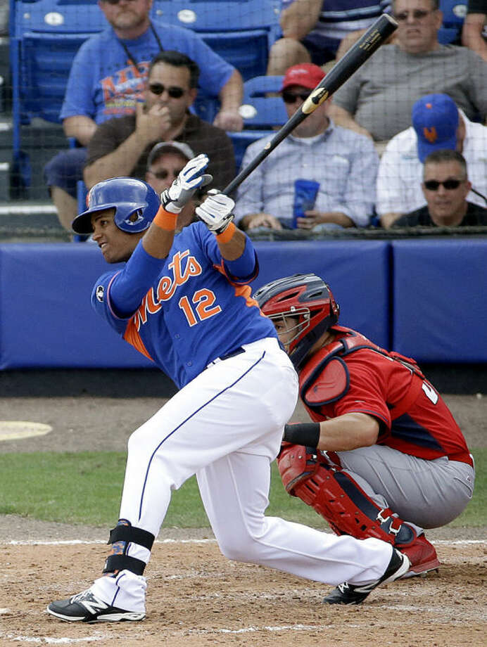 New York Mets' Juan Lagares hits a single to score teammates Eric Campbell and Andrew Brown in the seventh inning of an exhibition spring training baseball game against the St. Louis Cardinals, Wednesday, March 12, 2014, in Port St. Lucie, Fla. (AP Photo/David Goldman)