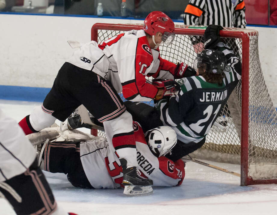 JOSH GIBNEY PHOTO Connecticut's Nick Jermain (21) gets tangled up between Northern's Tony Crow (10) and goaltender Jimmy Poreda during the second period of Wednesday's EHL championship final series game at Cyclones Arena in Hudson, N.H..