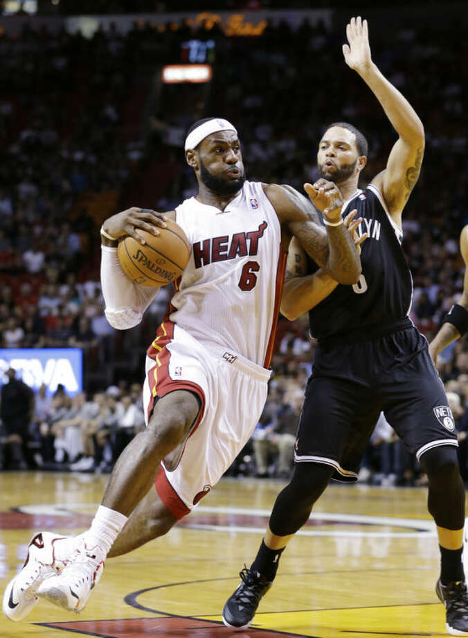 Miami Heat forward LeBron James (6) goes up for a shot against Brooklyn Nets guard Deron Williams during the first half of an NBA basketball game, Wednesday, March 12, 2014, in Miami. (AP Photo/Wilfredo Lee)