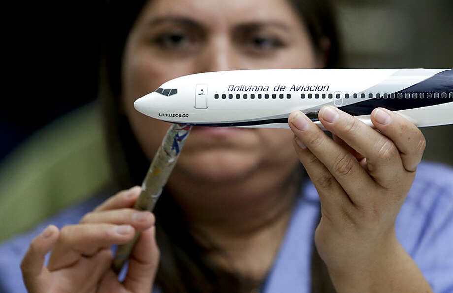 In this Feb. 5, 2015 photo, Diocelina Barajas applies decals to a model plane at Pacific Miniatures in Fullerton, Calif. When airlines open new routes, make deals with other carriers or finance new jets, there is a gifting of high-quality models. They are used to break the ice at difficult meetings, are tremendous marketing tools and a favored way of saying thank you. (AP Photo/Chris Carlson)