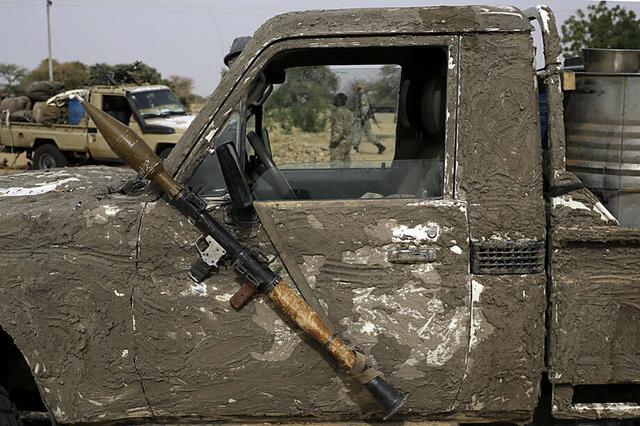 A rocket propelled launcher hangs on the mirror of a camouflaged Chadian pickup truck in the Nigerian city of Damasak, Nigeria, Wednesday, March 18, 2015. Damasak was flushed of Boko Haram militants last week, and is now controlled by a joint Chadian and Nigerien force. (AP Photo/Jerome Delay)