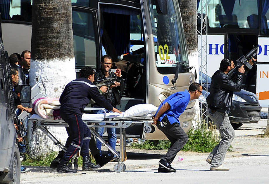 Escorted by security forces, rescue workers pull an empty stretcher outside the Bardo museum Wednesday, March 18, 2015 in Tunis, Tunisia. Authorities say scores of people are dead after an attack on a major museum in the Tunisian capital, and some of the gunmen may have escaped. (AP Photo/Salah Ben Mahmoud)