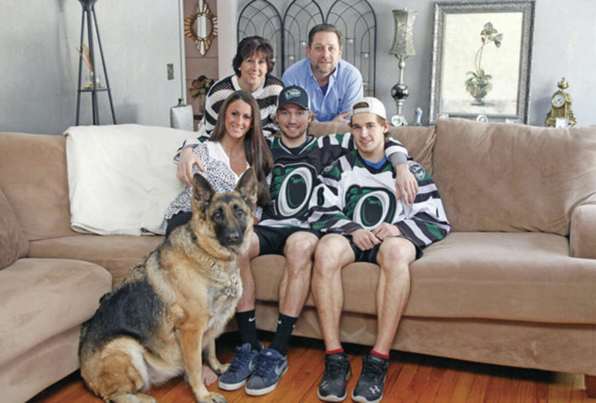 Bill & Kim Forcier, their daughter Alison and family dog pose for a photo with Connecticut Oliers players Ryan Fitzgerald and Roman Pfennings who they hosted for the season at their home in Norwalk Sunday afternoon. Hour Photo / Danielle Calloway