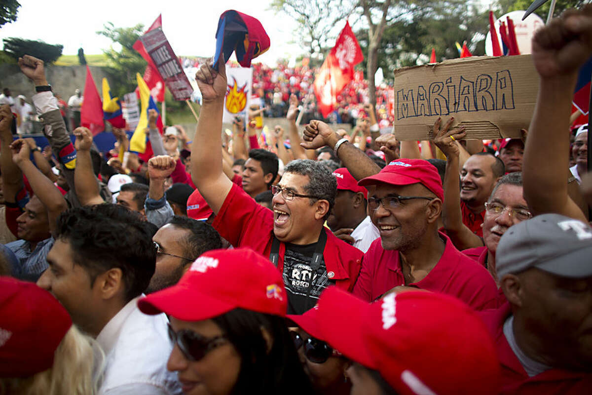State oil and electric workers shout slogans during an anti-imperialist rally at Miraflores presidential palace in Caracas, Venezuela, Wednesday, March 18, 2015. The rally was held amid tensions between Venezuela and the U.S. after President Nicolas Maduro this month said Washington is plotting to oust him and ordered the U.S. Embassy in Caracas to slash staffing levels. The U.S. later levied sanctions against seven Venezuelan officials accused of human rights violations. (AP Photo/Ariana Cubillos)