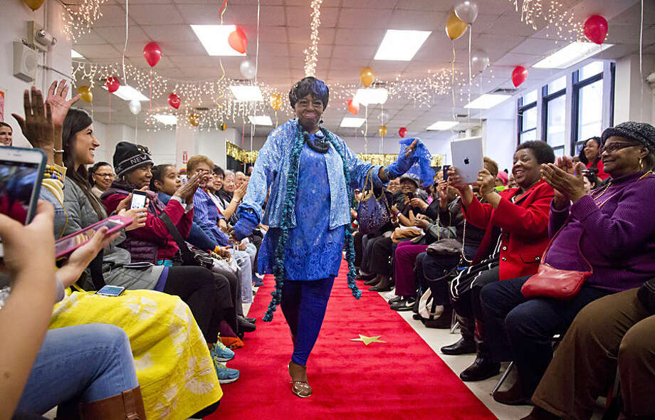 Rachel Oddman, 63, struts the runway to a cheering crowd at the Carter Burden-Leonard Covello Senior Program 2nd Annual Fashion Show, Wednesday, March 18, 2015, in the East Harlem section of New York. The program, which aims to promote the well-being of seniors 60 and older through a wide range of activities, includes a sewing class where some seniors make clothes to wear on the runway. (AP Photo/Bebeto Matthews)