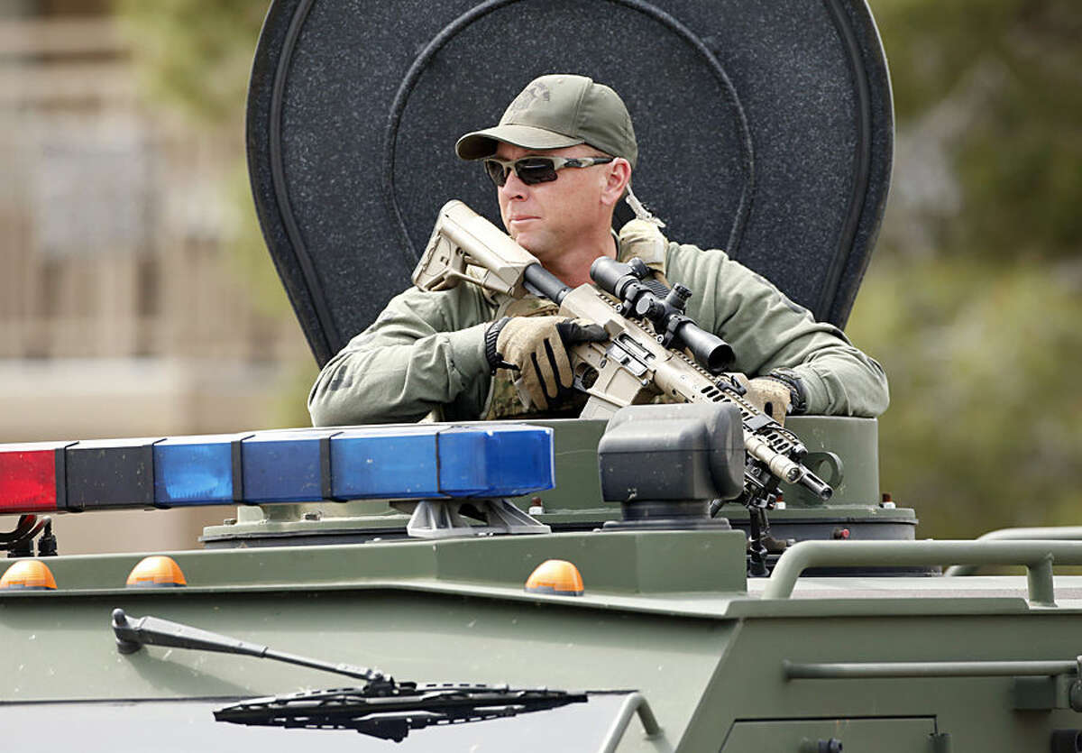 A SWAT team member searches for a gunman from the top of an armored truck Wednesday, March 18, 2015, in Mesa, Ariz. A gunman in a rampage that included a motel shooting, a carjacking and a home invasion ended with his arrest at a nearby apartment in suburban Phoenix. (AP Photo/The Arizona Republic, Rob Schumacher)