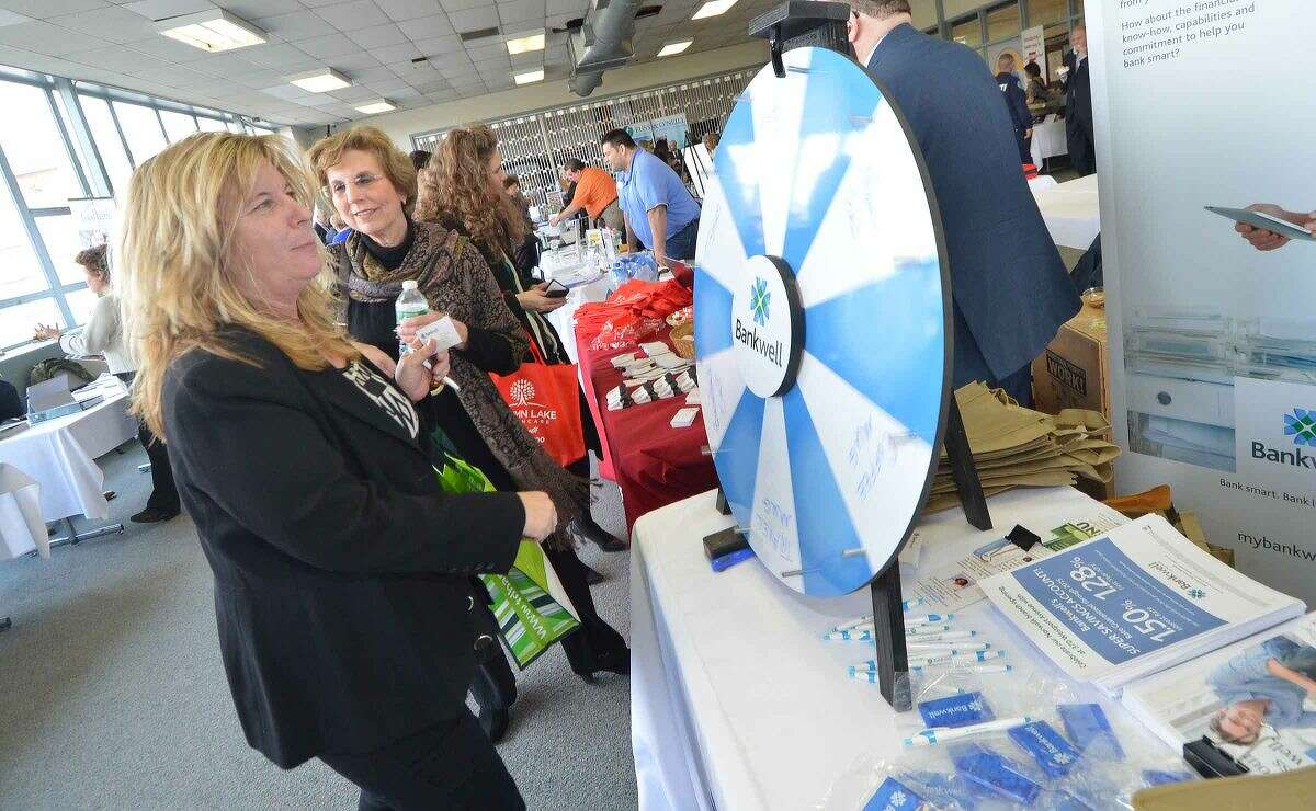 Hour Photo/Alex von Kleydorff Kathy Derrico spins the wheel and wins a cap at the Bankwell booth during the 2015 Multi Chamber Expo and Networking event at NCC,