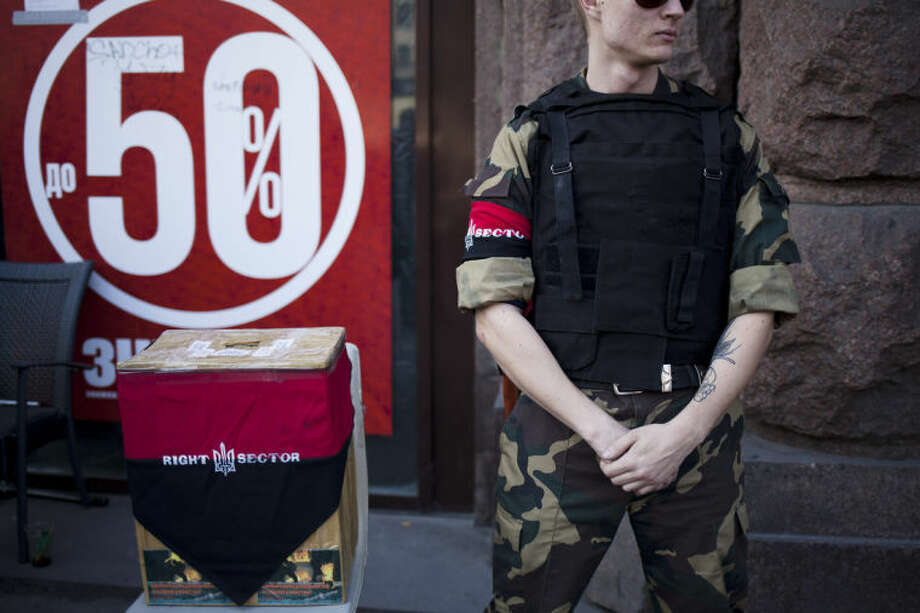 In this photo taken Tuesday, March 11, 2014, a member of the Right Sector stands alongside a donation box outside a store which the group is occupying near Kiev's Independence Square, Ukraine. Several weeks after mass protests ousted Russian-leaning President Viktor Yanukovych, hundreds of members of the radical ultranationalist group, the Right Sector, continue to patrol central streets and occupy buildings in Kiev, while some more radical members have burst into regional government offices, brandishing rifles, harassing bureaucrats and even punching a prosecutor. (AP Photo/David Azia)