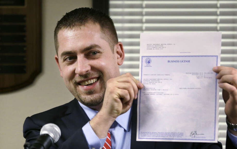 FILE -- In this March 5, 2014 file photo, Sean Green displays his newly-issued Washington state legal marijuana license in Olympia, Wash. One of the U.S. Justice Department's top concerns in allowing Washington and Colorado to move forward with plans to legalize and tax marijuana sales is seeing that the states keep criminals out of the industry. But the DOJ itself is refusing to let Washington run national background checks on those applying to run legal pot businesses, The Associated Press has learned, and those who have received the first legal pot licenses have done so without going through a national background check. (AP Photo/Elaine Thompson, File)