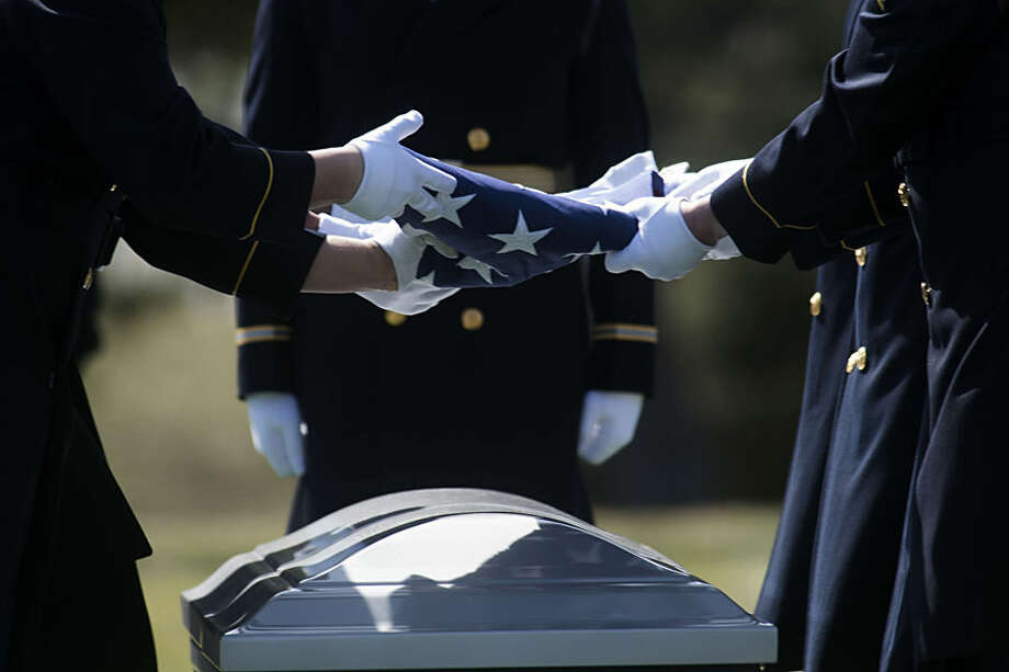 Members of the honor guard fold a flag above the casket holding the remains of eight Airmen missing from World War II during burial services at Arlington National Cemetery in Arlington, Va. Wednesday, March 18, 2015. The remain of the eight Airman, Army Air Forces 1st Lt. William D. Bernier, Army Air Forces 1st Lt. Bryant E. Poulsen, Army Air Forces 1st Lt. Herbert V. Young Jr., Army Air Forces Tech Sgt. Charles L. Johnston, Army Air Forces Tech Sgt. Hugh F. Moore, Army Air Forces Staff Sgt. John E. Copeland, Army Air Forces Staff Sgt. Charles J. Jones, and Army Air Forces Sgt. Charles A. Gardner were buried as a group in a single casket. (AP Photo/Kevin Wolf)