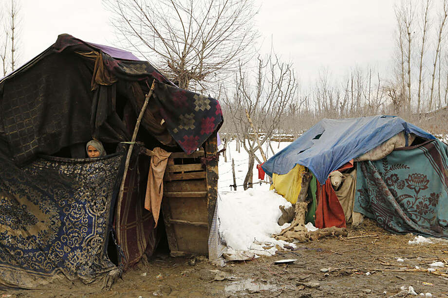 A young Kashmiri Bakarwal nomad girl looks out from inside her temporary camp, with a sheep in the adjoining tent at Haal village, some 52 Kilometers (33 miles) south of Srinagar, India, Wednesday, March 18, 2015. The Jammu-Srinagar highway, connecting the Kashmir valley to the rest of the country, remained closed for the fourth consecutive day Wednesday following heavy rain and snowfall at some places. (AP Photo/Mukhtar Khan)