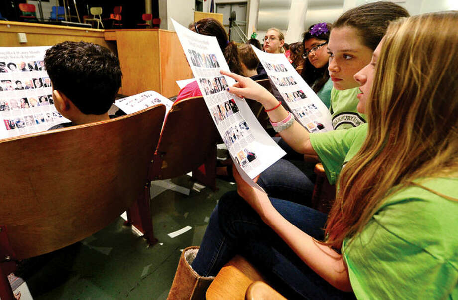 "Hour photo / Erik Trautmann West Rocks Middle School 6th graders Jordan Hogan and olivia Caputo listen to a presentation by George Albano, The Hour's Associate Sports Editor, as he speaks to 6th graders at the school Friday about his ""Celebrating Black History Month Through Norwalk Sports"" series, which was published in The Hour during the month of February."