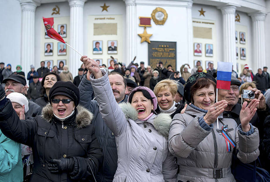 Local residents wave Russian flags as they greet Black Sea fleet sailors marching during a military parade in Sevastopol, Crimea, Wednesday, March 18, 2015. Russia on Wednesday marked the one year anniversary of the annexation of Ukraine's Crimea peninsula. (AP Photo/Mikhail Mordasov)