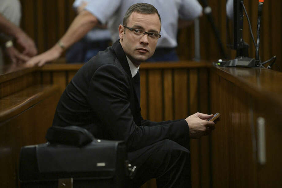 Oscar Pistorius sits in the dock during his murder trial at a court in Pretoria, South Africa, Friday, March 14, 2014. Pistorius is charged with the shooting death of his girlfriend Reeva Steenkamp, on Valentines Day in 2013. (AP Photo/Phill Magakoe, Pool)