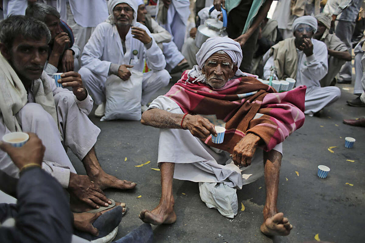 Indian farmers drink tea as they gather near the parliament for a protest against the ruling Bharatiya Janata Party's Land Acquisition Bill in New Delhi, India, Wednesday, March 18, 2015. Opposition parties and farmers have marched in the capital and protested against the bill, calling it anti-farmer in a country where agriculture is the main livelihood for more than 60 percent of the 1.2 billion people. (AP Photo/Altaf Qadri)