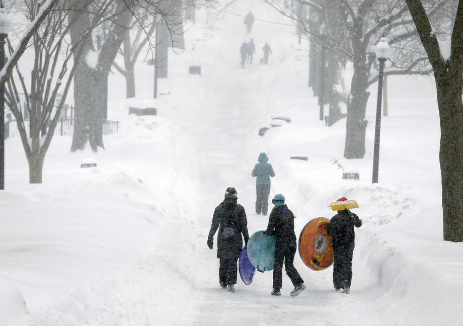 FILE - In this Feb. 9, 2015 file photo, people carry their sleds on Boston Common during a snowstorm in Boston. On the eve of spring, as New Englanders close the books on a relentless winter, The Associated Press asked a few hardy souls what 9 feet of snow taught them about life, love and human nature. (AP Photo/Steven Senne, File)