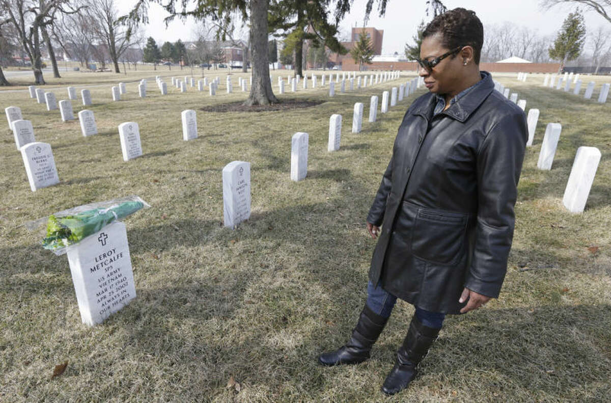 Dellaina Grundy gazes upon her father's headstone, Army veteran Leroy Metcalfe, Saturday, March 8, 2014, at the Dayton National Cemetery in Dayton, Ohio. Grundy isn?'t sure whether any or all of the cremated remains buried in the grave are his and knows that mystery will never be solved.(AP Photo/Al Behrman)