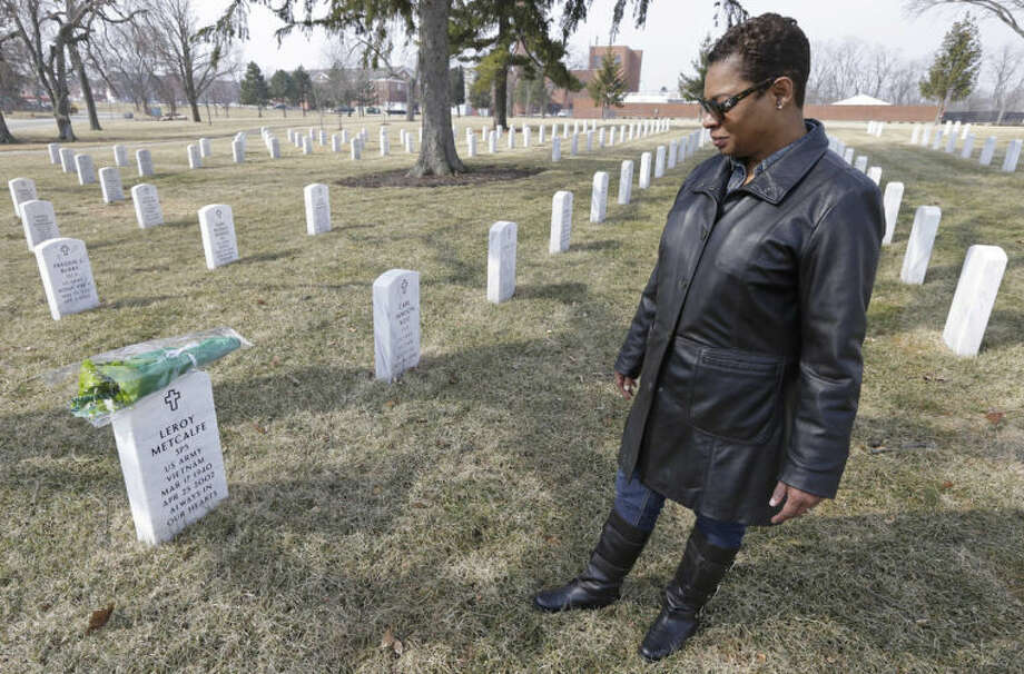 Dellaina Grundy gazes upon her father's headstone, Army veteran Leroy Metcalfe, Saturday, March 8, 2014, at the Dayton National Cemetery in Dayton, Ohio. Grundy isn't sure whether any or all of the cremated remains buried in the grave are his and knows that mystery will never be solved.(AP Photo/Al Behrman)