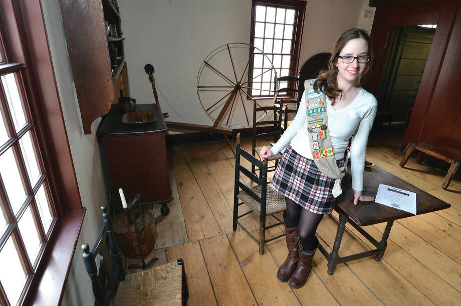 Emma Gosden with Girl Scout Troop 50400 in Wilton stands in a room at the Wilton Historical Society.