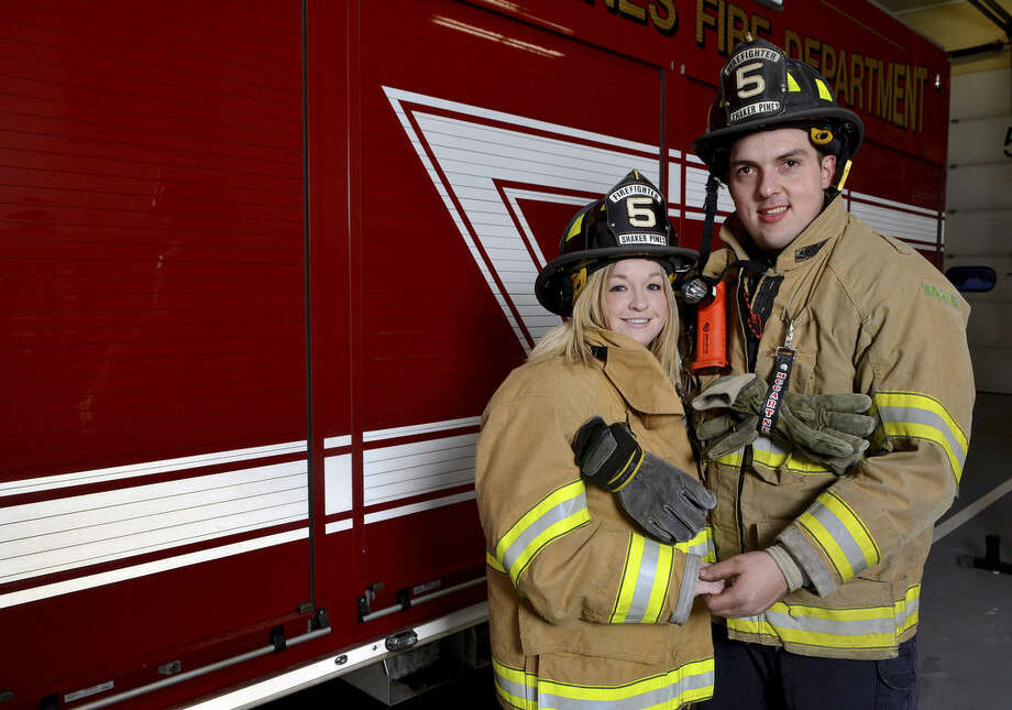 In this Feb. 12, 2015 file photo, Shaker Pines Fire Department, firefighters Melissa Greczkowski, left, and her fiancé Damian McCartney pose for a photograph at the firehouse in Enfield, Conn. McCartney planned to propose during an elaborate, staged training drill outdoors. But when the first of 2015's blizzards struck, they had to revert to an alternative plan indoors. (AP Photo/The Hartford Courant, Marc-Yves Regis I)