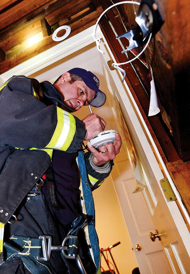 Hour photo / Erik Trautmann Norwalk Fire Department Lieutenant Chris Riccio replaces smoke detectors at home of elderly Norwalk resident Robert Jones Friday.