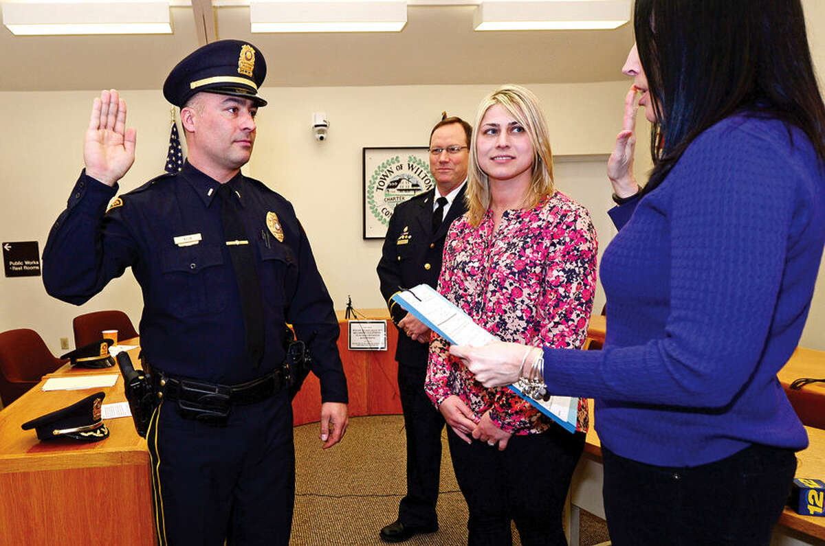 Hour photo / Erik Trautmann Lieutenant Robert Kluk of the Wilton Police Department is sworn in by Town Clerk, Lori Kaback, during his promotion ceremony as acting Chief Robert Crosby and Kluk's wife, Emily, look on Friday morning.