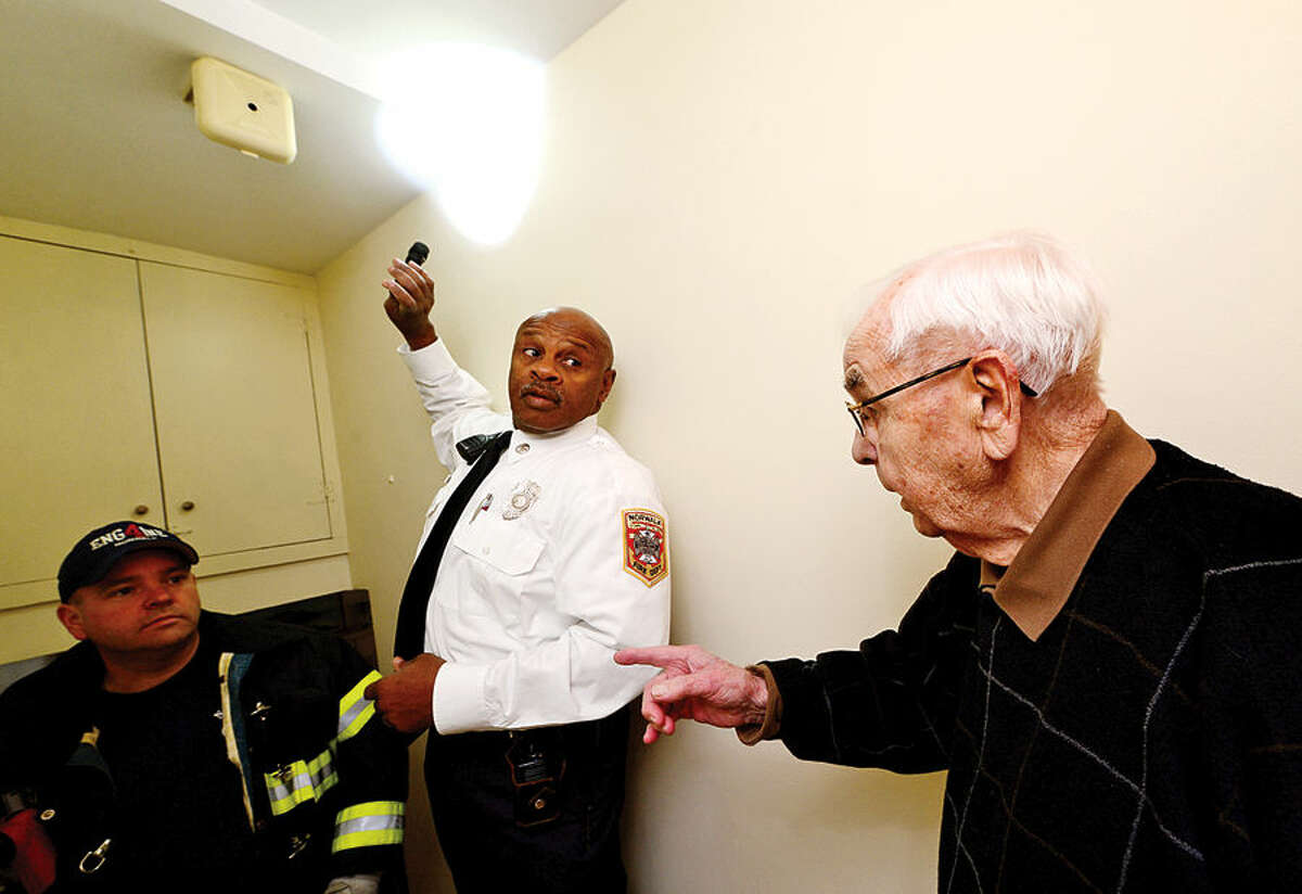 Hour photo / Erik Trautmann Norwalk Fire Department Deputy Fire Marshal Broderick Sawyer and firefighter Michael Delaney replace smoke detectors at home of elderly Norwalk resident Robert Jones Friday.