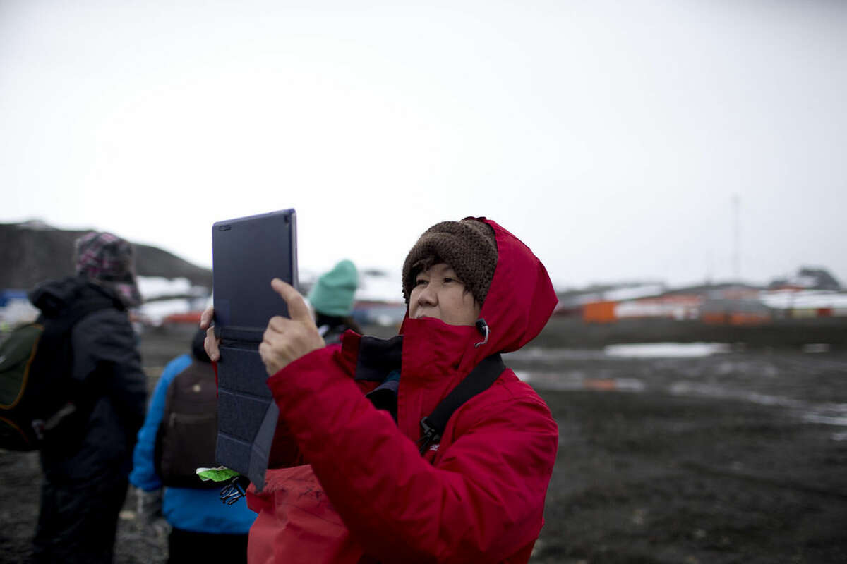 In this Feb. 2, 2015 photo, a tourist uses a tablet to make a picture after disembarking from the Ocean Nova cruise ship, on King George Island, Antarctica. Most visitors arrive on the Antarctic Peninsula, accessible from southern Argentina and Chile by plane or ship. The next most popular destination is the Ross Sea on the opposite side of the continent, which visitors reach after sailing 10 days from New Zealand or Australia. (AP Photo/Natacha Pisarenko)