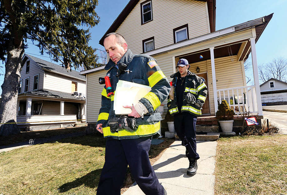 Hour photo / Erik Trautmann The Norwalk Fire Department's Captain Adam Markowitz and firefighter Anthony Papacoda go door-to-door urging neighbors of the woman who died from burns suffered in yesterday's blaze on Ely Ave to make sure they have smoke detectors and are following fire safety precautions.