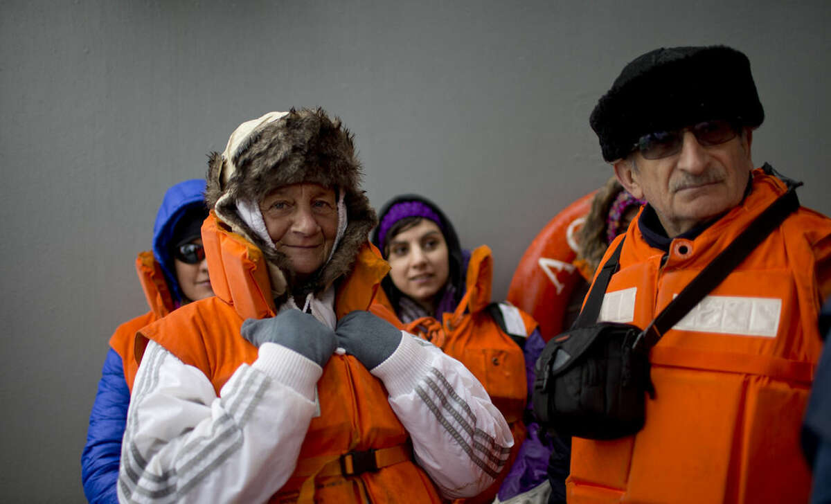 In this Jan. 22, 2015 photo, Chilean tourists Estela Dorion, left, and Renato Valenzuela, wait on the deck of The Aquiles, a Chilean Navy icebreaker, for a zodiac that will transport them to the Bernardo O'Higgins scientific station, Antarctica. The harsh environment requires vacationers to come with many essentials: water-resistant hiking boots, several layers of winter clothes including long underwear and a parka, and powerful sun lotion and dark shades with extra ultraviolet protection. (AP Photo/Natacha Pisarenko)