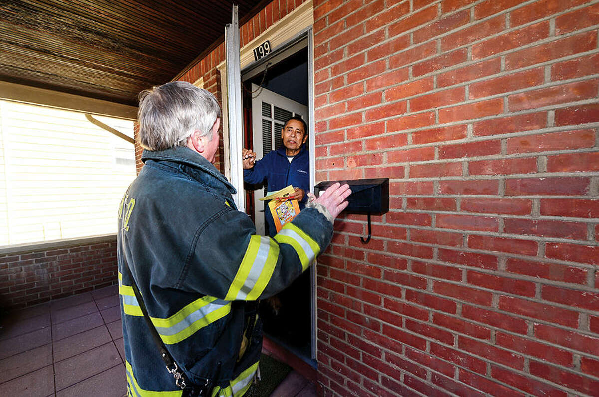 Hour photo / Erik Trautmann The Norwalk Fire Department's Fire Inspector KIrk McDonald urges neighbors of the woman who died from burns suffered in yesterday's blaze on Ely Ave including Lionel Mayorga to make sure they have smoke detectors and are following fire safety precautions.