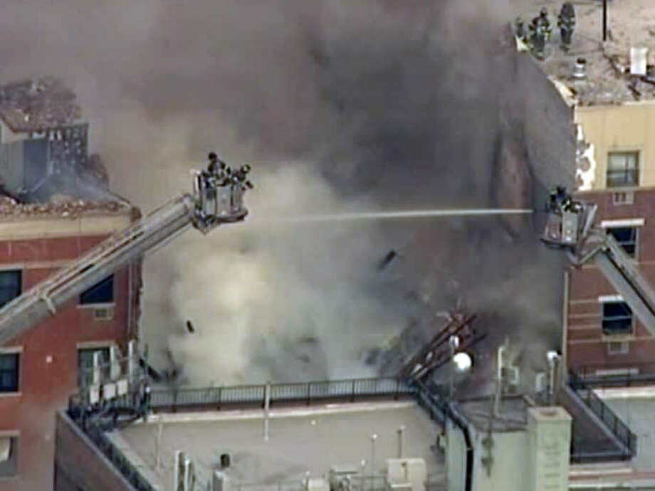 In this image taken from video from WABC, firefighters battle a blaze at the site of a possible explosion and building collapse in the East Harlem neighborhood of New York, Wednesday, March 12, 2014. (AP Photo/WABC-TV)
