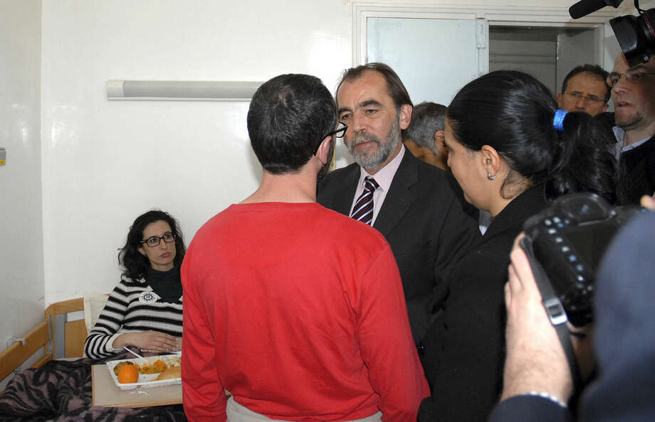 Spanish tourist Cristina Rubio, left, who is four months pregnant, looks at Tunisian Health Minister Saïd Aïdi speaking to her companion Juan Carlos Sanchez, as she rests at the maternity ward of the Charles Nicolle hospital in Tunis, Tunisia, Thursday March 19, 2015. As gunmen fired on tourists Wednesday, Sanchez, in red, and Rubio, stayed in hiding all night, hours after police killed the two gunmen and the National Bardo museum's other visitors were escorted to safety. (AP Photo/Torkhani)